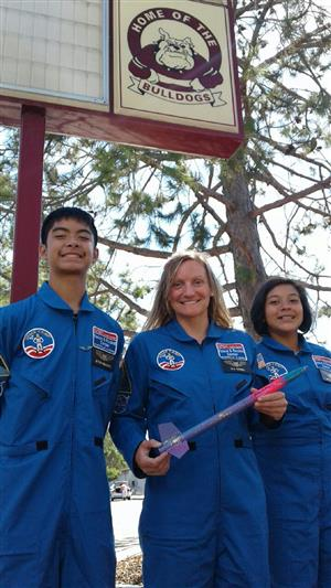 Treyton Kealalio-Puli, Teacher Julia Shotwell, and Marely Esquivel in their space suits that they got to take home with them