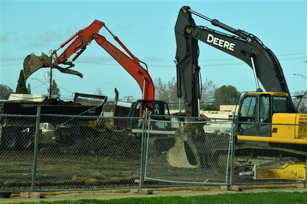 Construction equipment clears demolition debris to make way for new construction