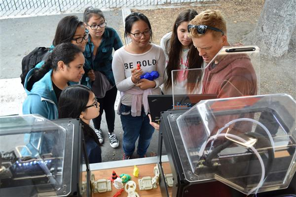 Santa Clara University student shows Columbia Middle students how a 3D printer works